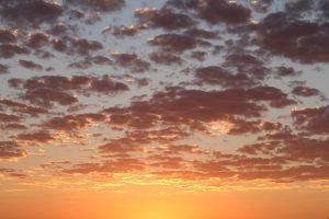 Sunrise with orange colour on a cloudy sky